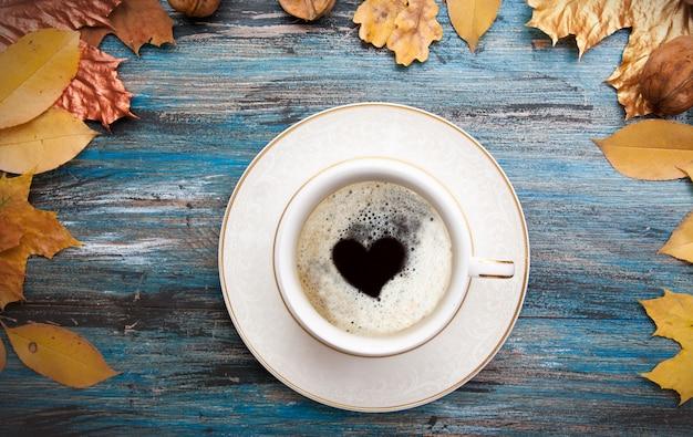 Diseño de otoño, una taza de café con un corazón dentro de la espuma, hojas de color naranja y dorado sobre fondo de madera azul vintage