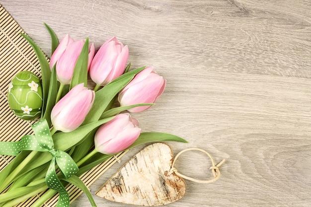 Diseño de pascua con tulipanes, huevo y corazón de madera.