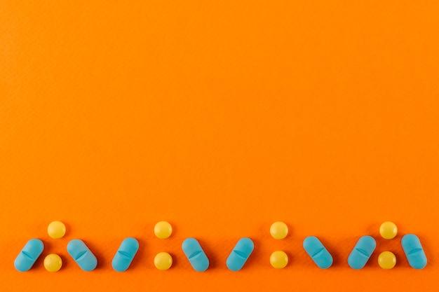 Diseño de pastillas hecho en un fondo de color naranja.