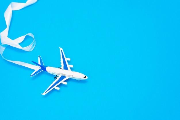 Diseño plano del concepto de viaje con avión sobre fondo azul con espacio de copia.
