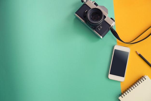 Diseño plano creativo de la endecha del concepto del viaje con el cuaderno, el lápiz, la cámara y el teléfono móvil en blanco en color en colores pastel amarillo y verde.