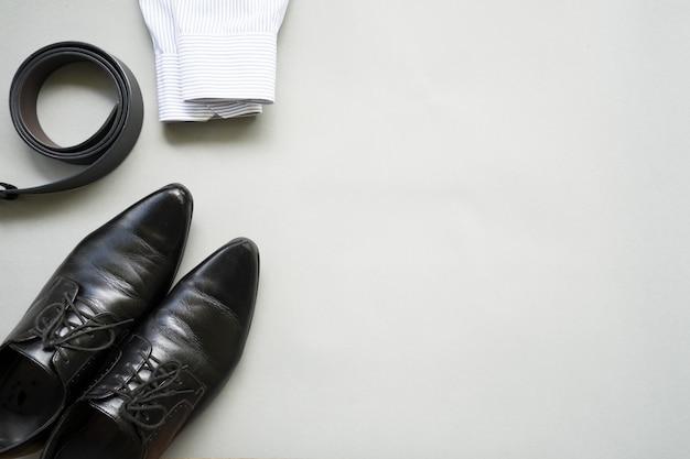 Diseño plano endecha de ropa de hombre de negocios con sobre fondo gris