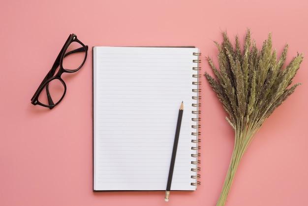 Diseño plano del escritorio del espacio de trabajo con gafas de lápiz de cuaderno en blanco y flor seca sobre fondo de color pastel vintage.
