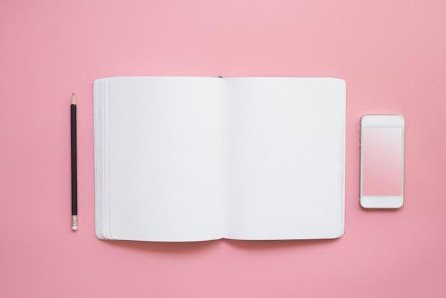 Diseño plano del escritorio del espacio de trabajo con lápiz de cuaderno en blanco y teléfono móvil sobre fondo rosa de color pastel vintage.