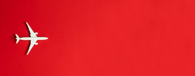 Diseño plano laico. modelo del juguete del aeroplano en blanco en un fondo rojo con el espacio para el texto.