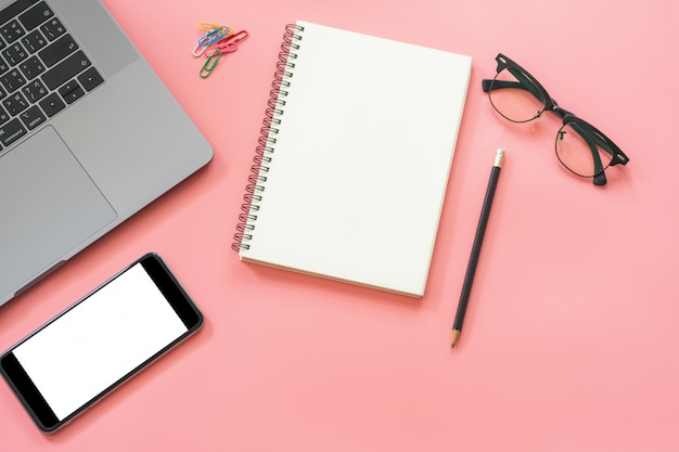 Diseño plano de la mesa de trabajo con computadora portátil, cuaderno en blanco, teléfono inteligente, lápiz, papelería