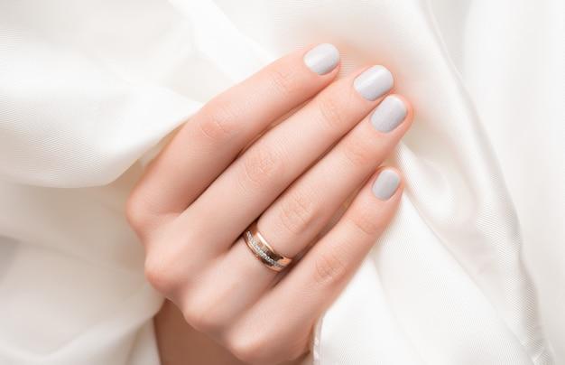 Diseño de uñas con purpurina. mano femenina con manicura gris.