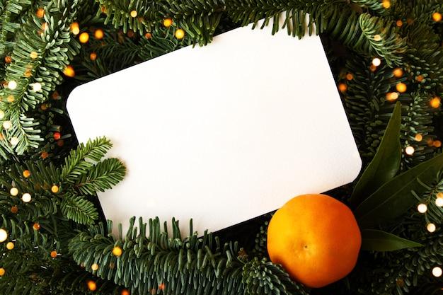 Diseño de ramas de árboles de navidad con tarjeta de papel blanco y mandarina fresca