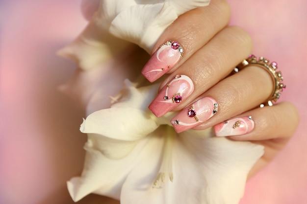 Diseño de uñas rosa claro con líneas blancas, pedrería, purpurina con gladiolos.