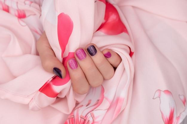 Diseño de uñas rosadas. cuidados mano femenina sobre fondo rosa.
