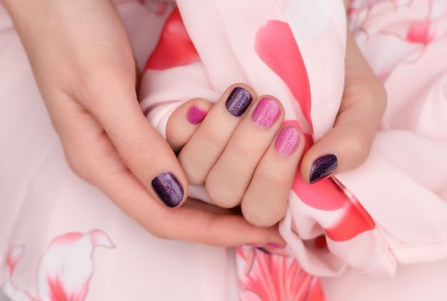 Diseño de uñas rosadas. cuidadosa mano femenina en rosa