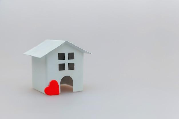 Diseño simplemente minimalista con casa de juguete blanca en miniatura con corazón rojo aislado en blanco