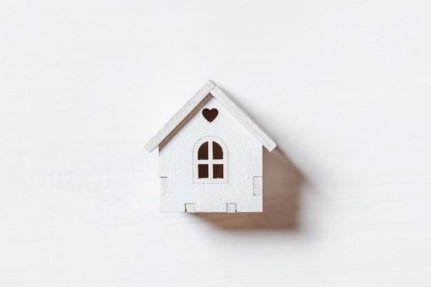 Diseño simplemente minimalista con casa de juguete en miniatura aislada sobre fondo blanco.