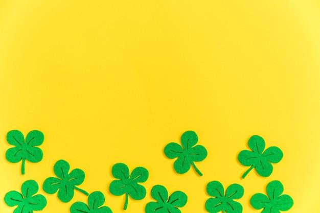 Diseño simplemente minimalista con hojas de trébol verde trébol aisladas sobre fondo amarillo