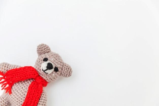 Diseño simplemente minimalista con oso de juguete en bufanda roja aislada sobre fondo blanco.