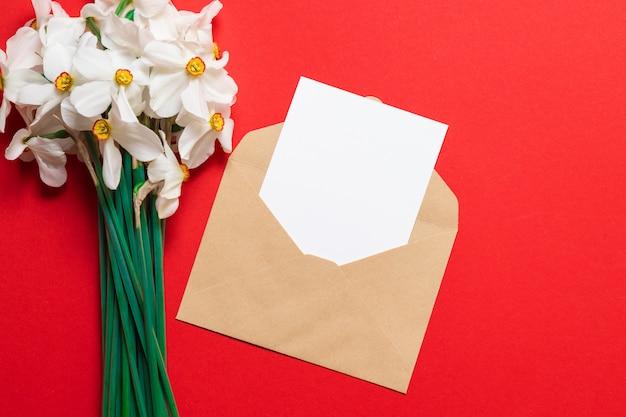 El diseño del sobre, flores de narcisos blancos frescos con tarjeta blanca.