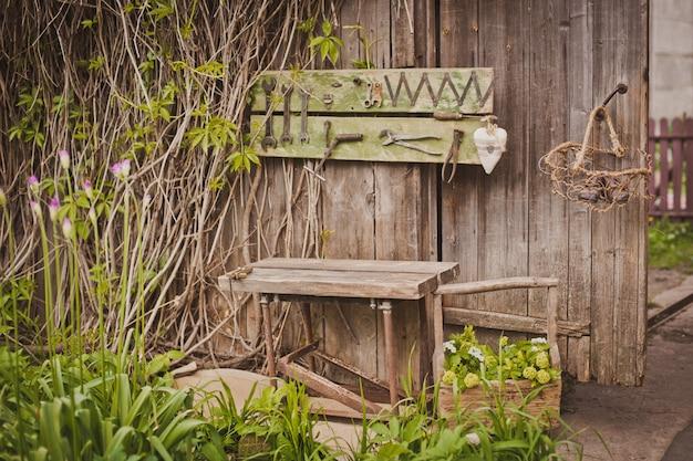 Diseño de la zona de fotos en un estilo rústico, antiguas puertas de madera y tablas con herramientas y flores de primavera.