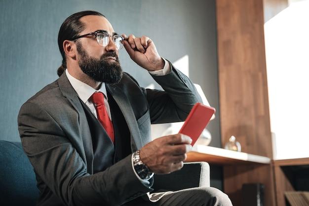 Disfraz y reloj. próspero hombre exitoso vestido con traje de negocios agradable y reloj de mano