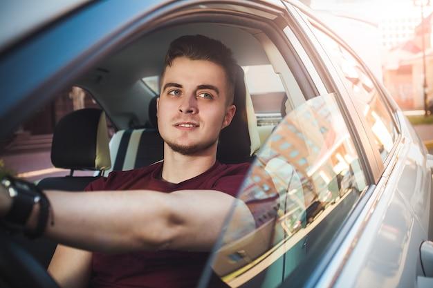 Disfruta la conducción. imagen de chico guapo joven sentado en el coche.