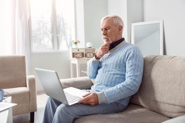 Disfruta leyendo. apuesto anciano sentado en el sofá y leyendo desde la pantalla del portátil mientras se rasca la barbilla, concentrándose en leer