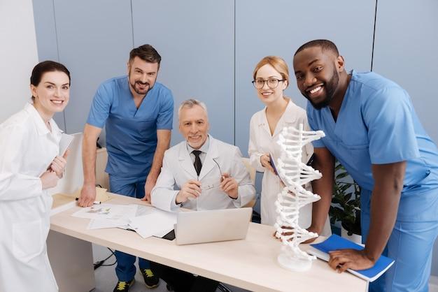 Disfrutando de la colaboración con aprendices dotados. médico calificado inteligente senior que trabaja y dirige la conferencia en la universidad mientras conversa con los aprendices y usa un gadget