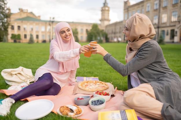 Disfrutando de la hora de la pizza. estudiantes musulmanes alegres que disfrutan de la pizza al aire libre y beben bebidas gaseosas