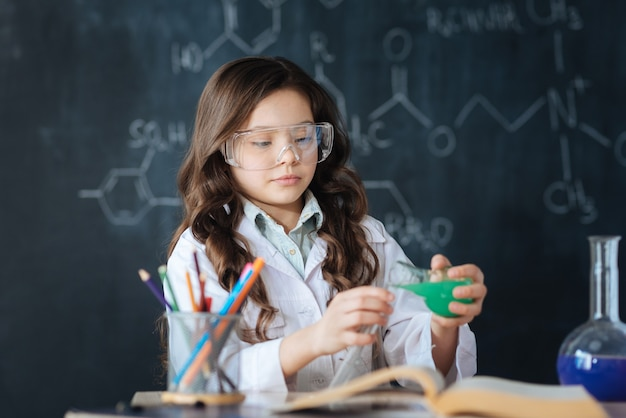 Disfrutando de mi futura profesión. talentoso niño hábil trabajador de pie en el laboratorio y disfrutando del experimento de química mientras participa en el proyecto de ciencias y explora la bombilla