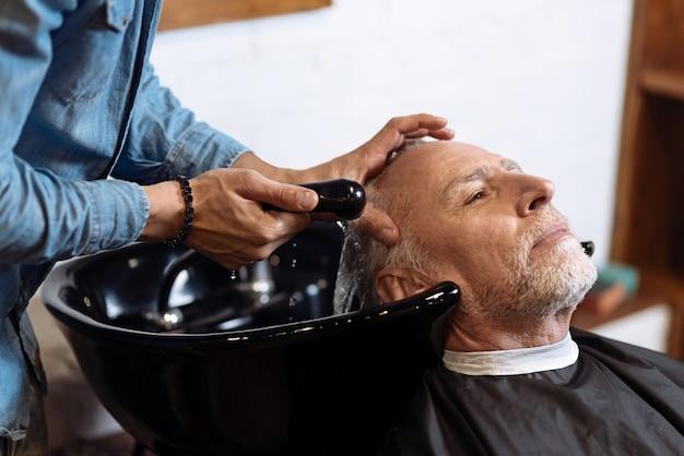 Disfrutando del proceso. cerca de senior hombre barbudo con su cabello lavado en peluquería.