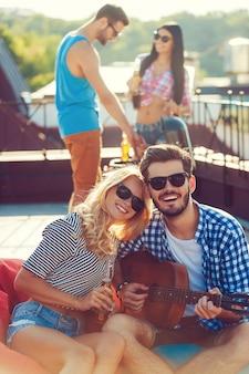 Disfrutando del tiempo con amigos. hermosa joven pareja pegada entre sí y sentada en la bolsa de frijoles con guitarra mientras dos personas hacen una barbacoa en el fondo