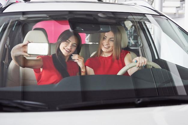 Disfrutando de viajar. hermosos gemelos de niña sentada en los asientos de los pasajeros delanteros y sonriendo mientras posan ante la cámara