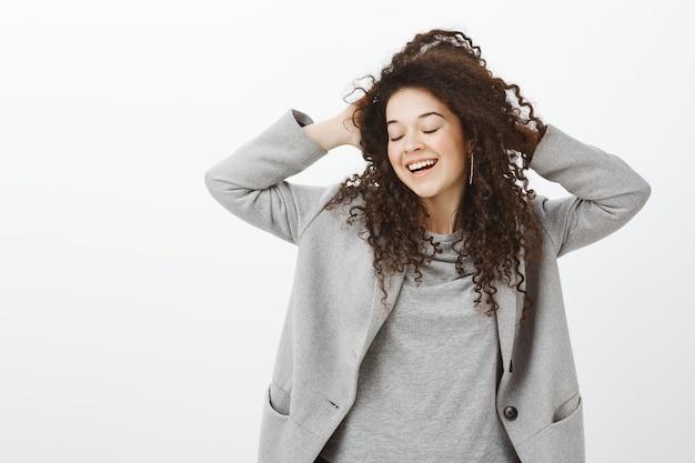 Disfrutando la vida al máximo. feliz niña soñadora femenina con cabello rizado, cerrando los ojos, tocando la cabeza, sonriendo con alegría, expresando una actitud tierna y tímida