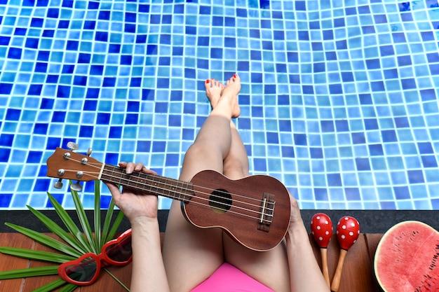 Disfrute de la brisa de verano, chica relajándose cerca de la piscina con fruta de sandía