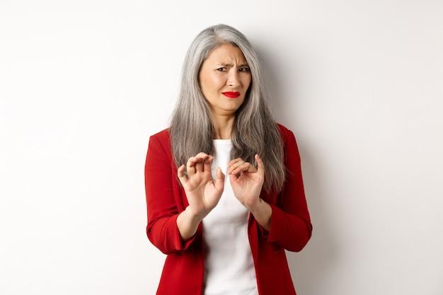 Disgustada empresaria asiática con cabello gris, vestido con blazer rojo y maquillaje, rechazando algo repugnante, mostrando la señal de stop, fondo blanco.