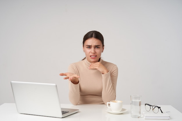 Disgustada joven empresaria bastante morena frunciendo el ceño y levantando emocionalmente la palma de su mano mientras mira, aislado sobre una pared blanca