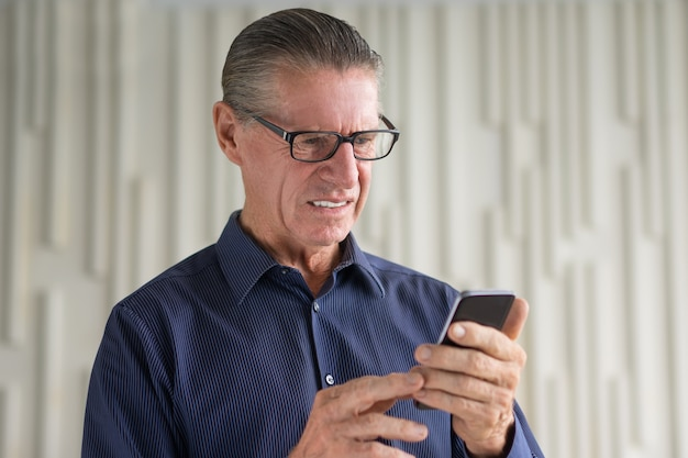 Disgustado hombre mayor mirando la pantalla del teléfono inteligente
