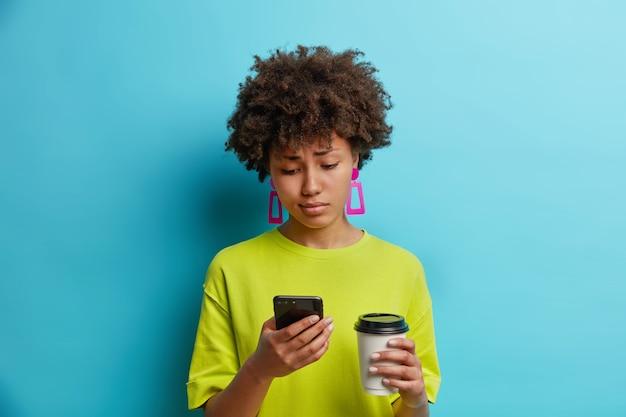 Disgustado joven bastante afroamericana mira con tristeza smartphone