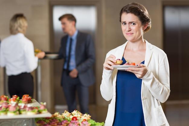Disgustado prueba de la mujer en la recepción snacks buffet