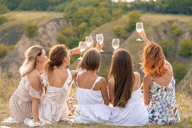 Dispara desde atrás. la compañía de hermosas amigas divirtiéndose, animando y bebiendo vino, y disfruta de un picnic en las colinas.