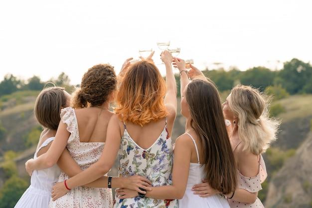 Dispara desde atrás. compañía de hermosas amigas divirtiéndose, animando y bebiendo vino, y disfruta de un picnic en las colinas.