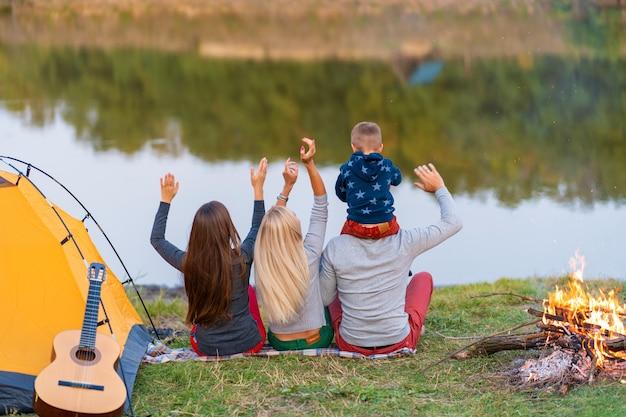 Dispara desde atrás. un grupo de amigos felices con un niño en el hombro acampando en la orilla del río, bailando, levanta las manos y disfruta de la vista. vacaciones familiares divertidas