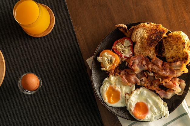 Dispara desde una vista superior, desayuno, receta fácil, huevos fritos, tocino, pimiento a la parrilla y pan en un plato negro sobre un paño blanco con una tira verde en la mesa de madera con huevo hervido y jugo de naranja