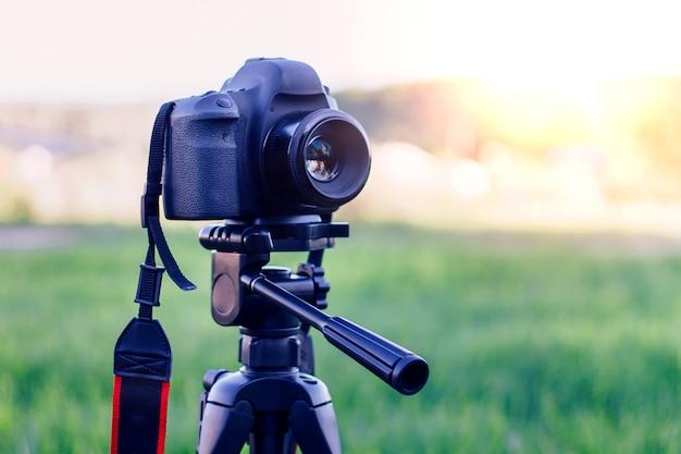Disparar una cámara al atardecer con un trípode en el parque