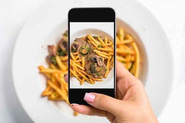 Disparar comida con la cámara del teléfono. carne con salsa de champiñones y patatas fritas. fotógrafo de alimentos, plato de disparo de teléfono de mano de primer plano