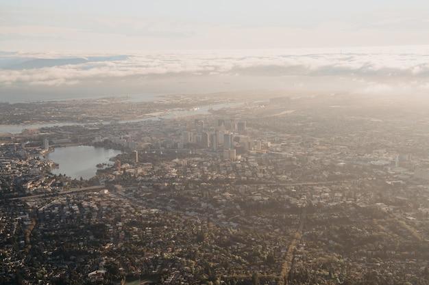 Disparo aéreo distante de una ciudad con rascacielos y un lago