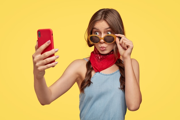 Disparo aislado de una adolescente de moda hace pucheros en los labios, mira a través de gafas de sol de moda, usa un pañuelo rojo cerca del cuello, sostiene un teléfono inteligente, hace un retrato selfie, disfruta del tiempo libre, se para sobre una pared amarilla