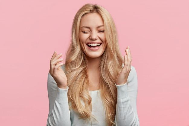 Disparo aislado de alegre joven rubia linda se ríe alegremente mientras escucha una anécdota divertida de un amigo, tiene el pelo largo y claro, posa contra la pared rosa. concepto de felicidad y emociones positivas