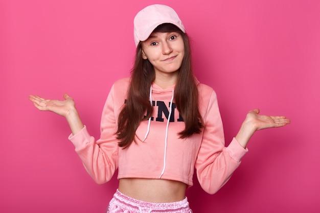 Disparo aislado de atractiva morena bonita adolescente, viste rosa con capucha y gorra