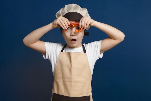 Disparo aislado de chico guapo lindo en uniforme de chef sosteniendo una rodaja de pimiento en su cara