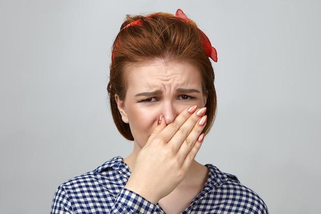 Disparo aislado de disgustada mujer caucásica joven atractiva en traje elegante haciendo muecas, pellizcando la nariz debido al olor apestoso de calcetines sucios o comida podrida. mal olor