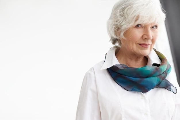 Disparo aislado de elegante mujer de negocios de edad avanzada de pelo blanco fasionable vistiendo elegante pañuelo de seda y camisa blanca formal con mirada de confianza